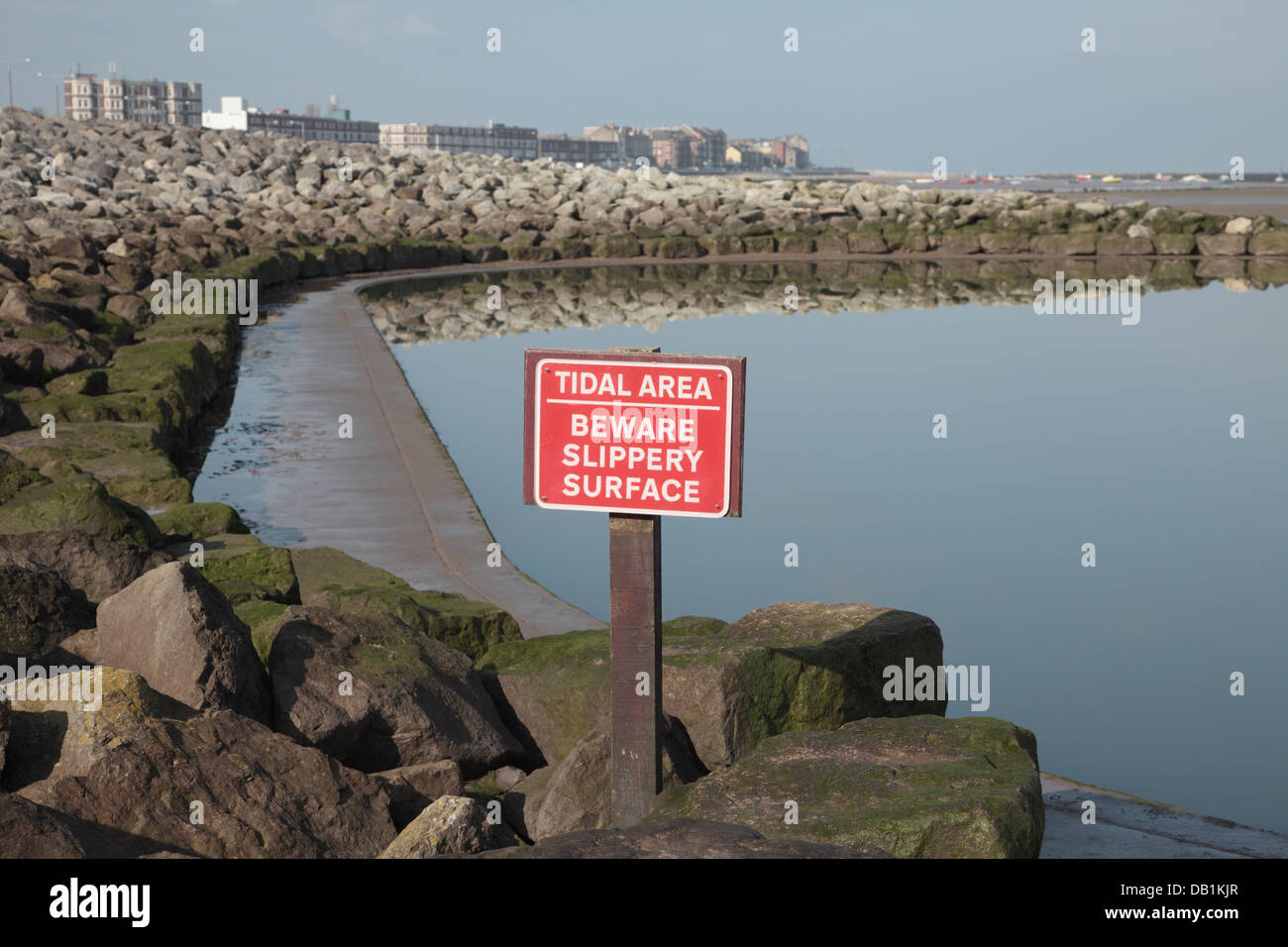 Sign 'Tidal Area-Beware Slippery Surface' next to boating pool - Stock Image