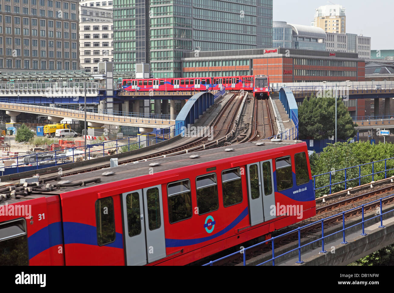 London Docklands Light Railway trains pass near West India Quay station - Stock Image
