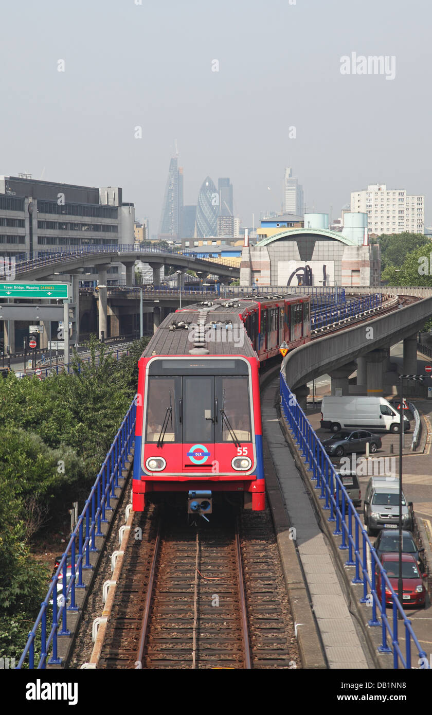 A London Docklands Light Railway train approaches Poplar station with the City of London in the background - Stock Image