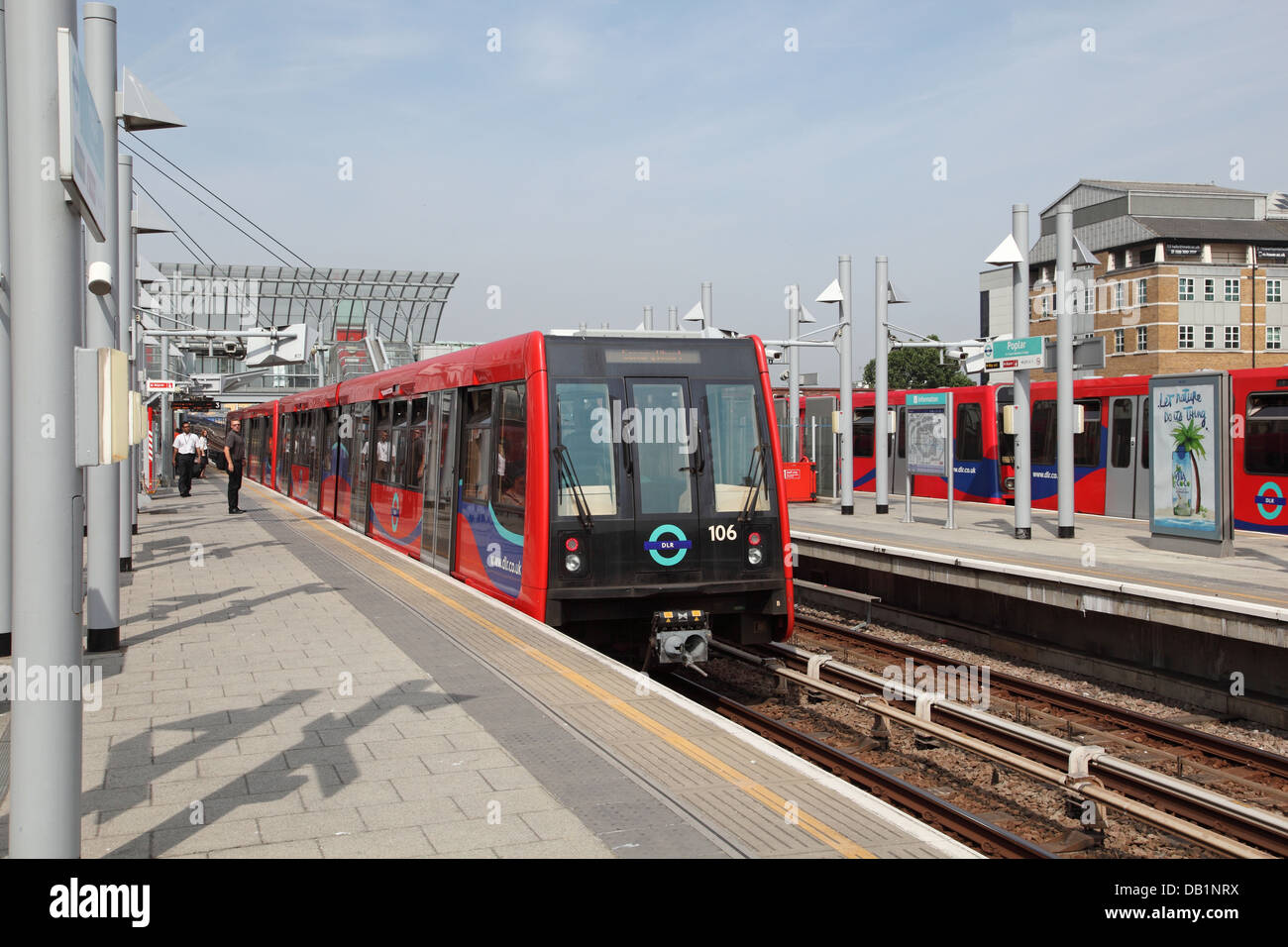 A London Docklands Light Railway train departs from Poplar Station - Stock Image