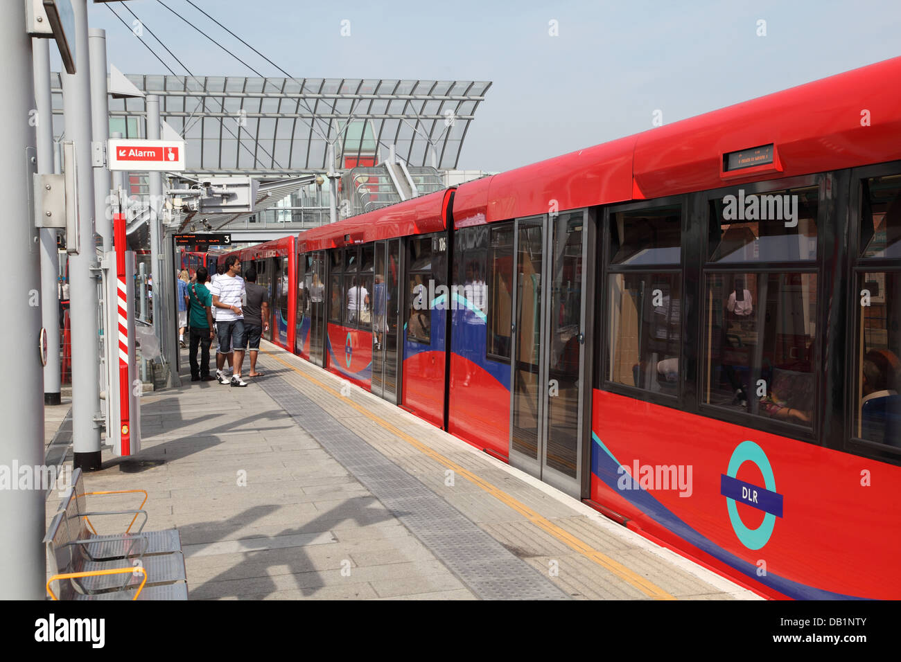 A London Docklands Light Railway train arrives at Poplar Station - Stock Image