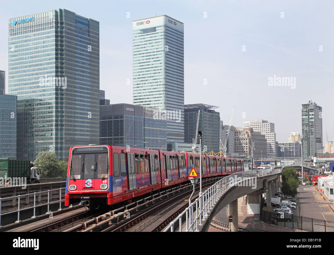 A London Docklands Light Railway train leaves Blackwall  station. Canary Wharf business district in the background - Stock Image