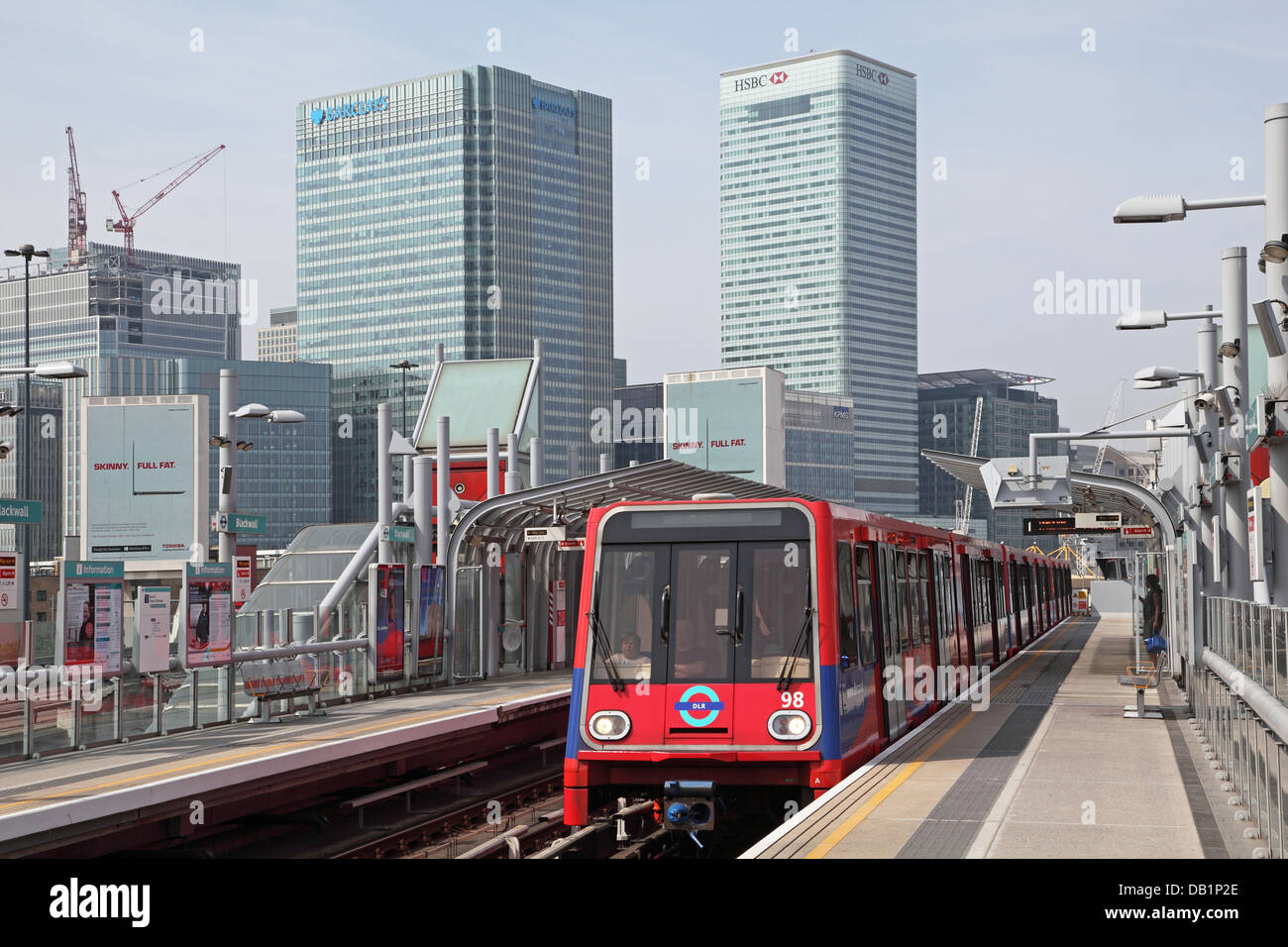 A London Docklands Light Railway train arrives at Poplar station with the Canary Wharf business district in the - Stock Image