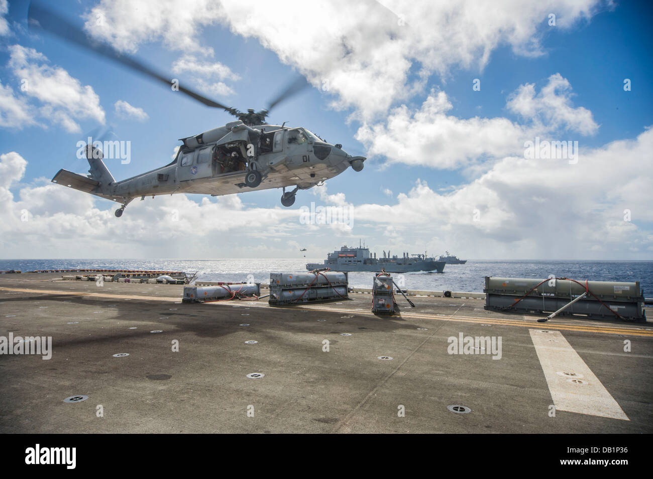 An SH-60S Sea Hawk helicopter assigned to the Island Knights of Helicopter Sea Combat Squadron (HSC) 25 loads supplies - Stock Image