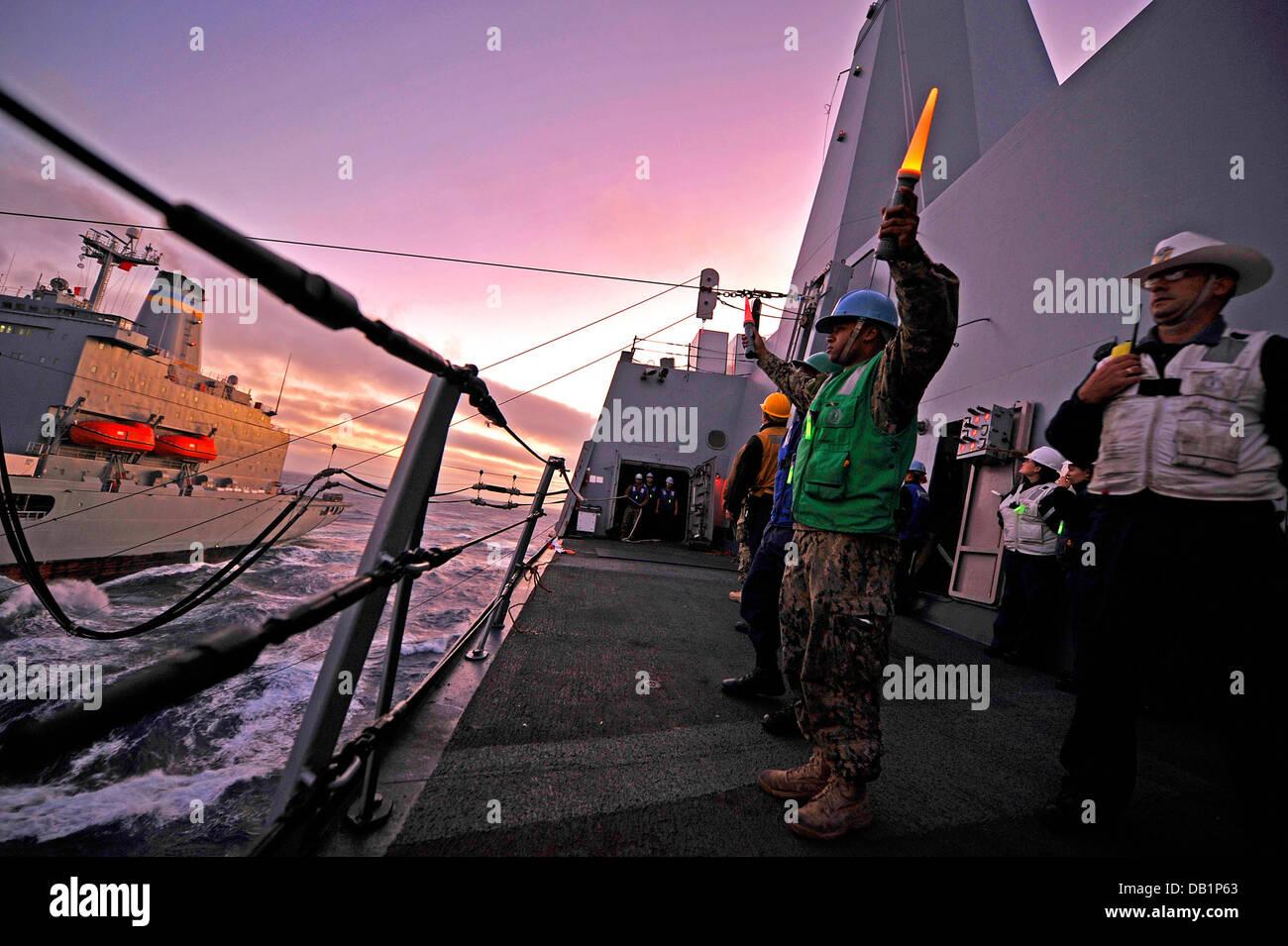 Boatswain's Mate 2nd Class Cory Shields signals to the Military Sealift Command fleet replenishment oiler USNS - Stock Image