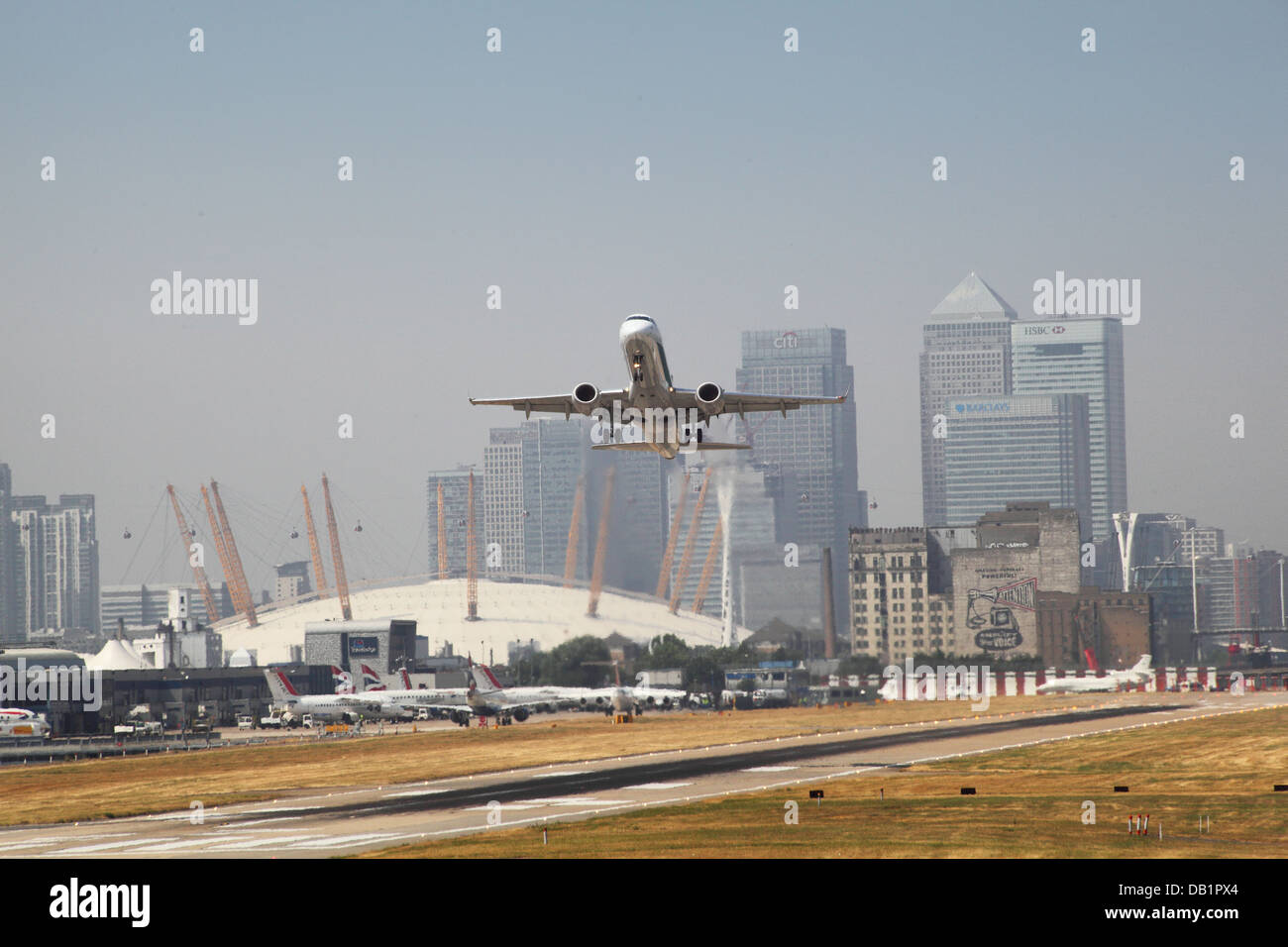 A passenger jet takes off from London City Airport with Canary Wharf and the Millennium Dome in background - Stock Image