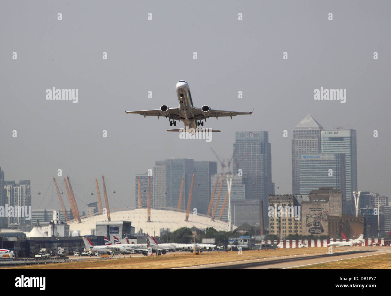 A passenger jet takes off from London City Airport with Canary Wharf and the Millennium Dome in the background - Stock Image
