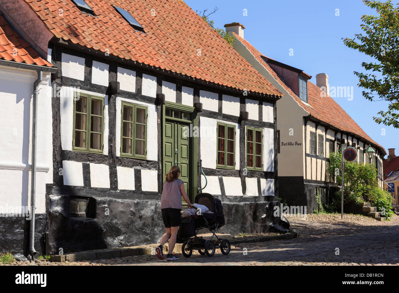 Woman pushing a pram over cobbles past quaint old houses on narrow cobbled street of Overgade, Ebeltoft, Jutland, - Stock Image