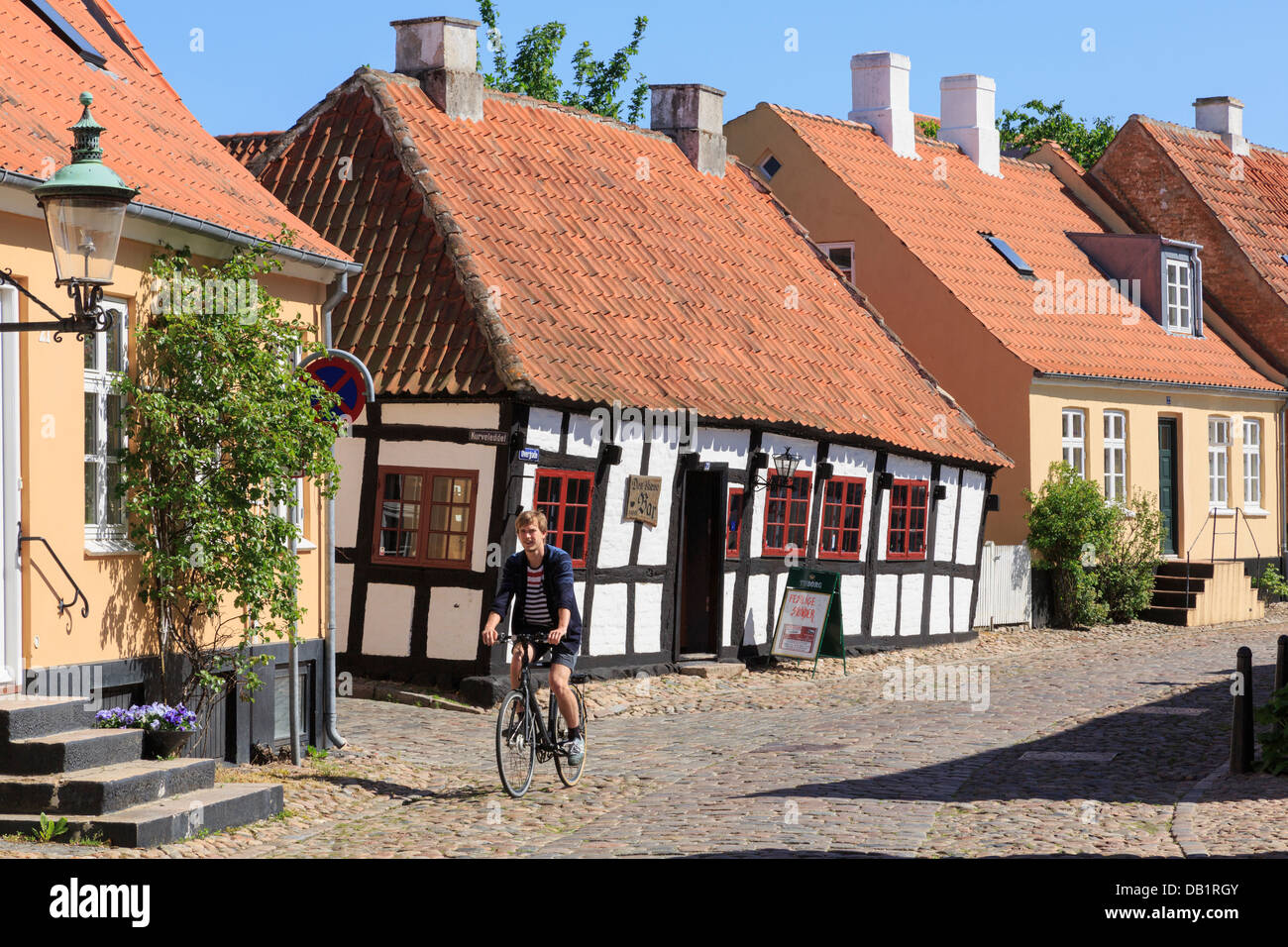 Quaint old Den skæve bar (The Crooked Bar) with man cycling on cobbles along cobbled street. Overgade Ebeltoft - Stock Image