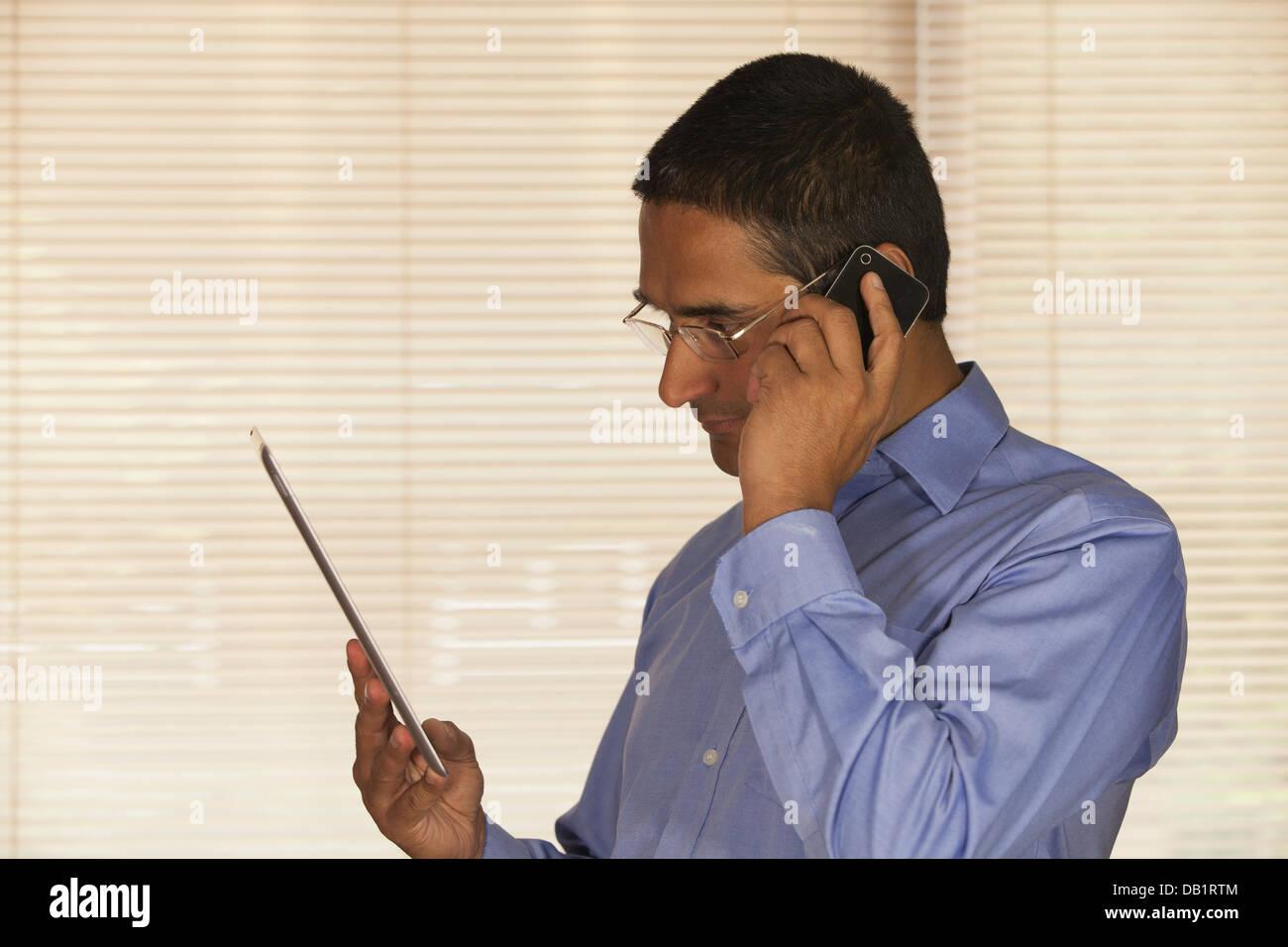 Man on Iphone looking at IPAD - Stock Image