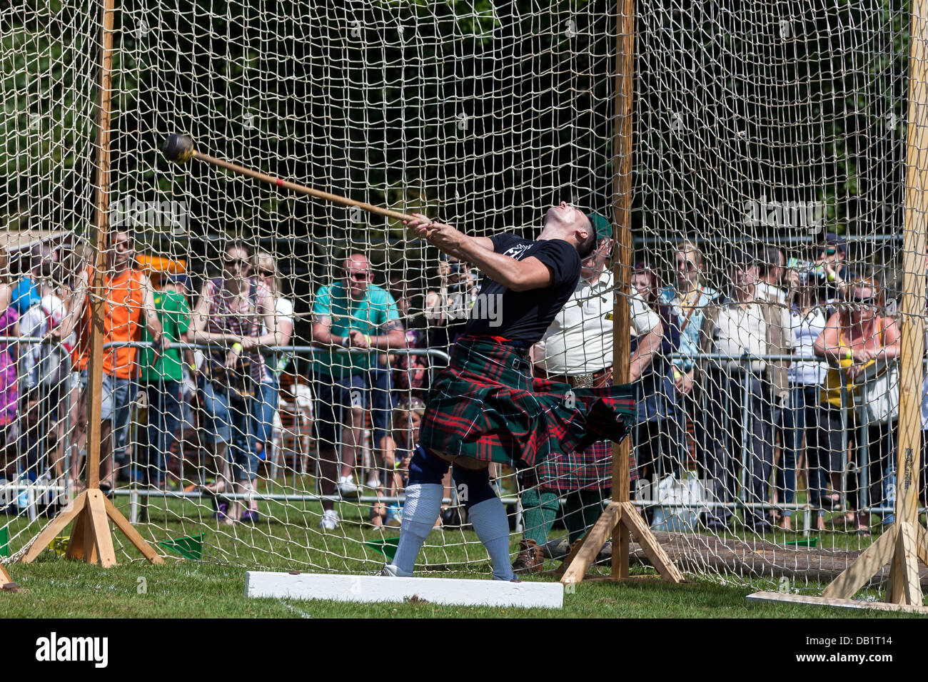 Competitor at Scottish highland games throwing the 22 pound hammer, a traditional Scottish competition. - Stock Image