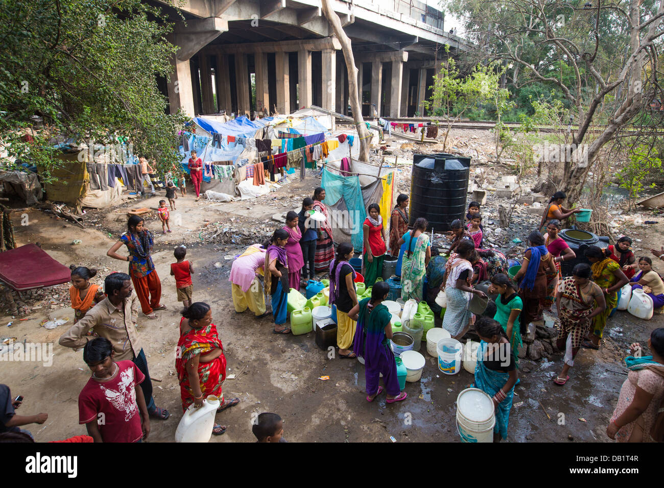 Women from tent village slums gather water after a government distribution, New Delhi, India - Stock Image