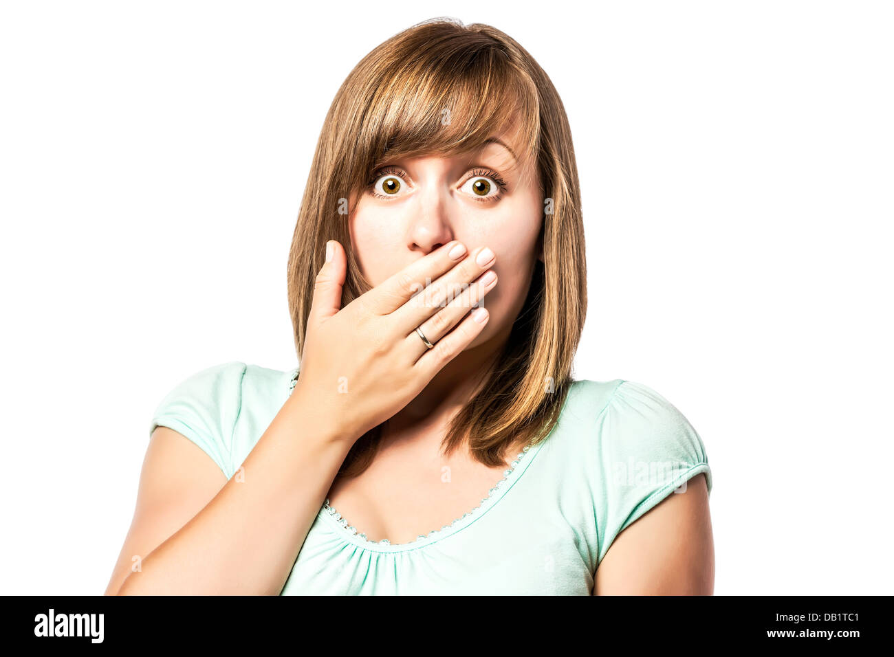 Shocked young girl who is afraid and keeps up with eyes wide open hand over her mouth, isolated on white background - Stock Image