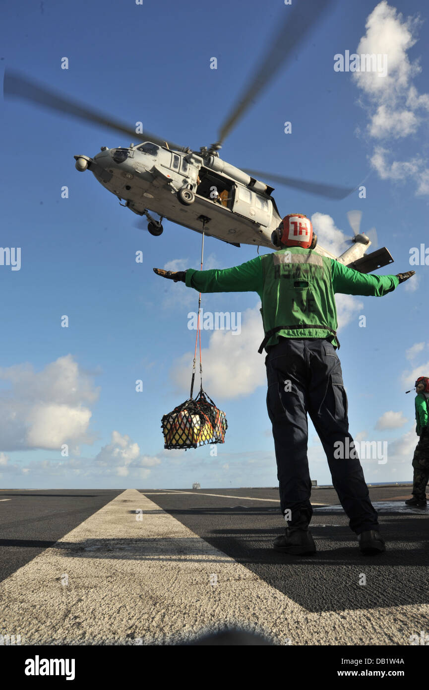 Aviation Structural Mechanic 2nd Class Justin Meiners, from Corona, Calif., uses hand gestures to direct an MH-60S - Stock Image