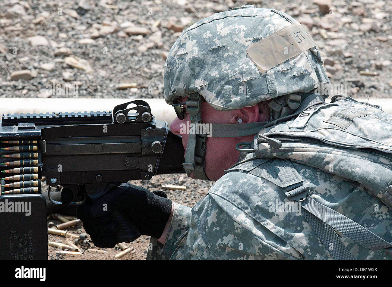 Brass and belt clips kick up dust as Sgt. Michael T. Crawford fires an M249 Machine Gun during familiarization training - Stock Image