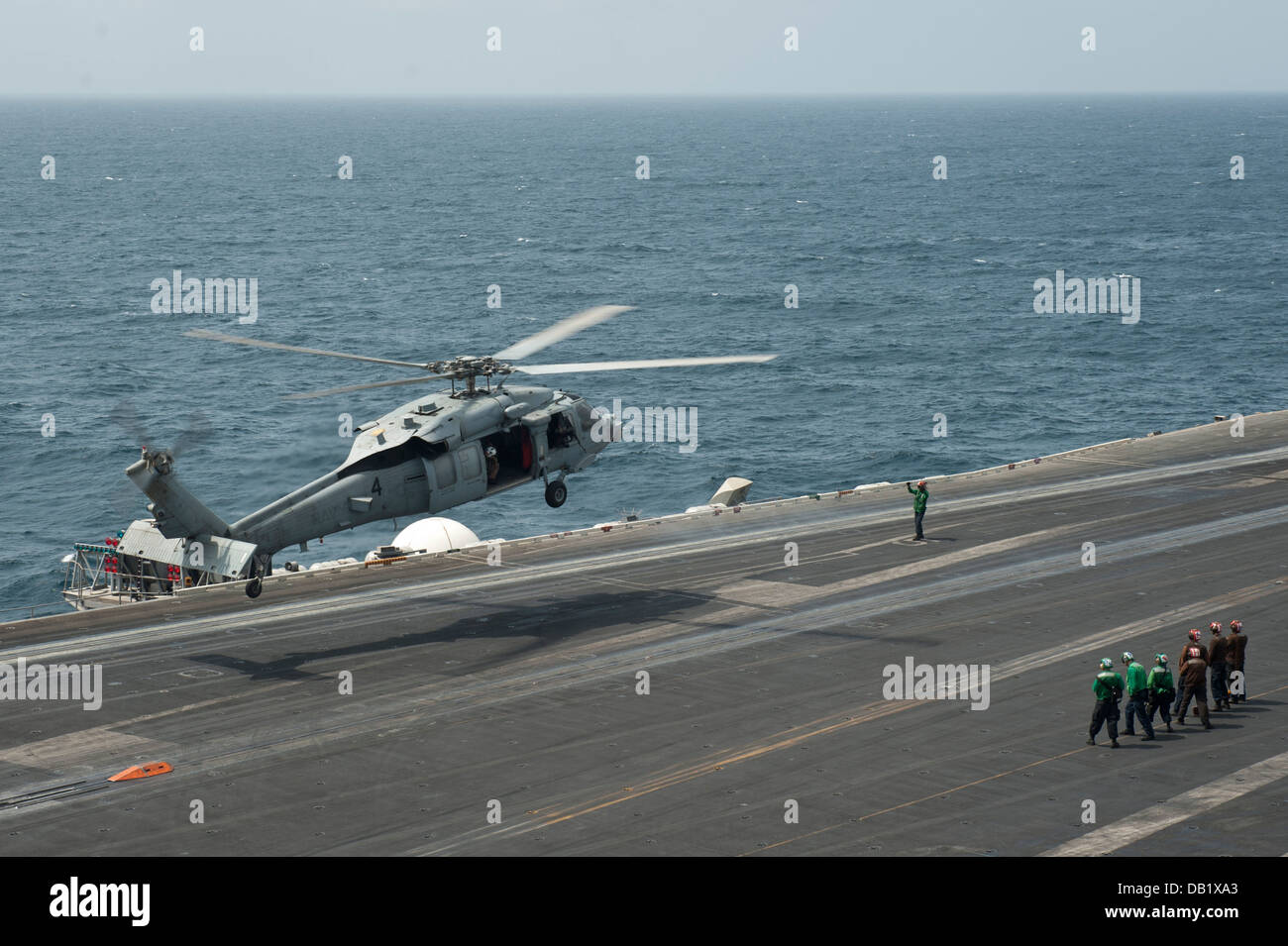 An MH-60S Sea Hawk helicopter assigned to the Indians of Helicopter Sea Combat Squadron (HSC 6) lands on the flight - Stock Image