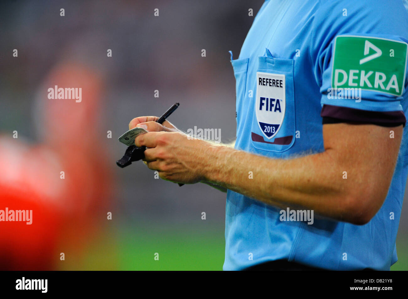 FIFA football referee notes a players name on his notepad - Stock Image