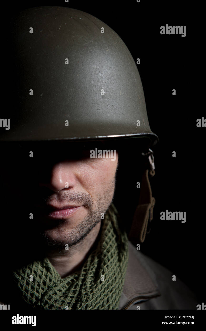 Spotlit portrait of a distraught WW2 American soldier against a black background. - Stock Image