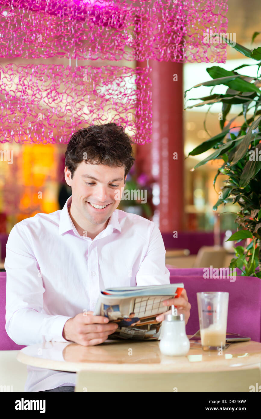 Young man in a cafe or ice cream parlor reading a magazine, maybe he is single or waiting for someone Stock Photo