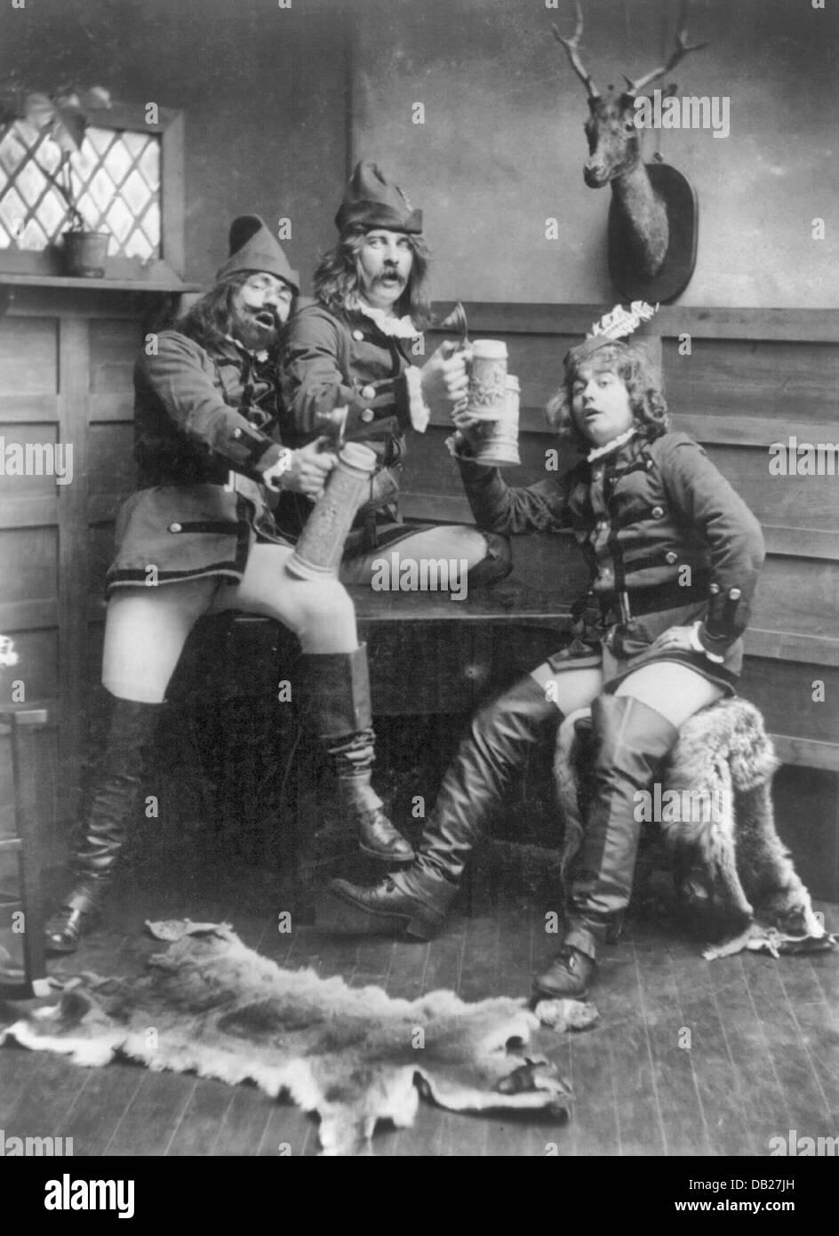 Three men in German student uniforms lifting beer steins, circa 1904 - Stock Image