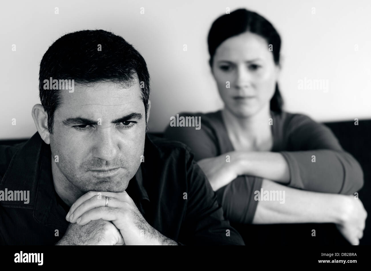 Portrait of unhappy young couple who have fallen out over a disagreement sitting on a sofa. Man in the front and - Stock Image