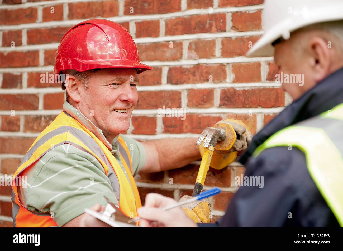 Two construction workers going about their duties. Site manager with a general workman, both talking and discussing - Stock Image