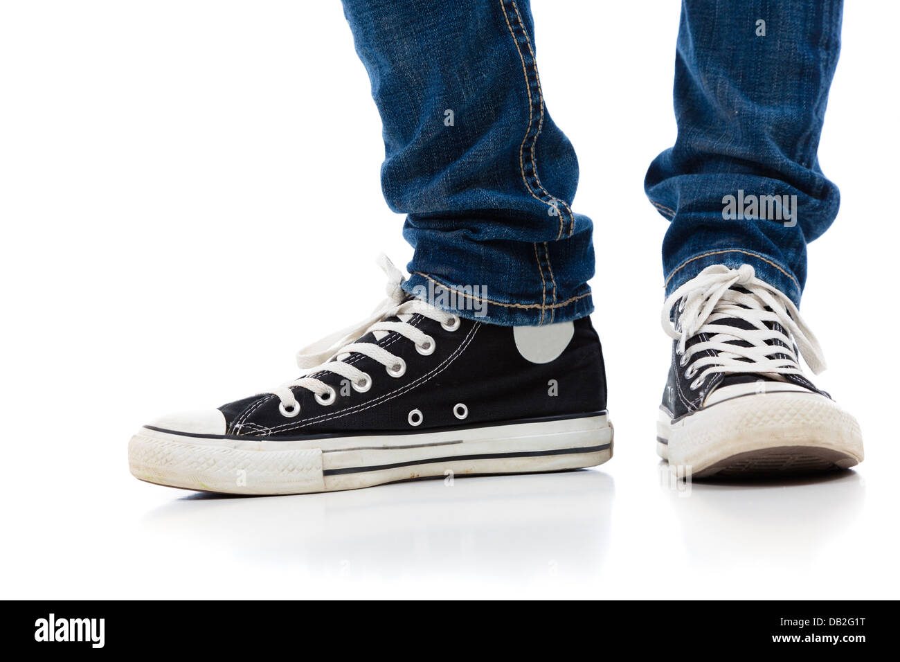 Legs With Tennis Shoes And Jeans On A White Background Stock Photo