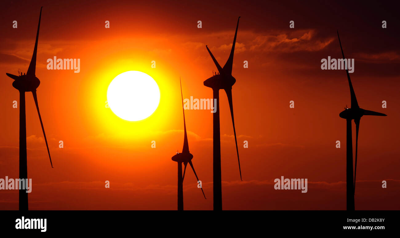 FILE - An archive picture dated 17 April 2011 shows the setting sun behind wind wheels near Tiefenthal, Germany. Stock Photo