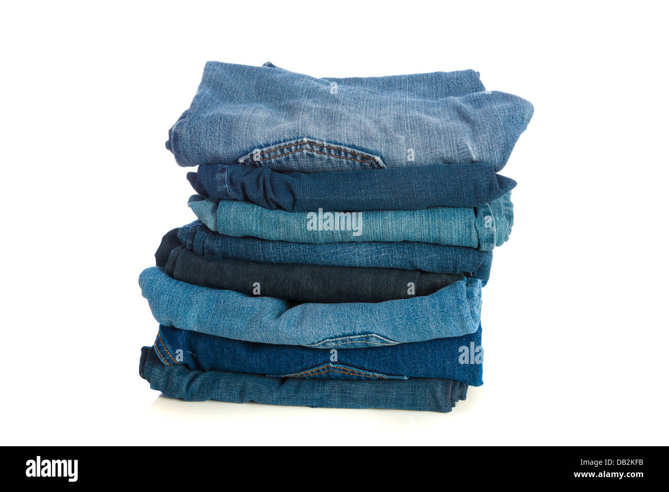 Stack of old blue jeans on a white background - Stock Image