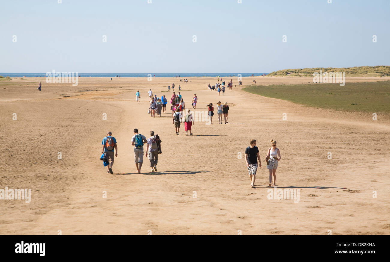 People walking to the sea across Wide sandy beach Holkham Norfolk England - Stock Image