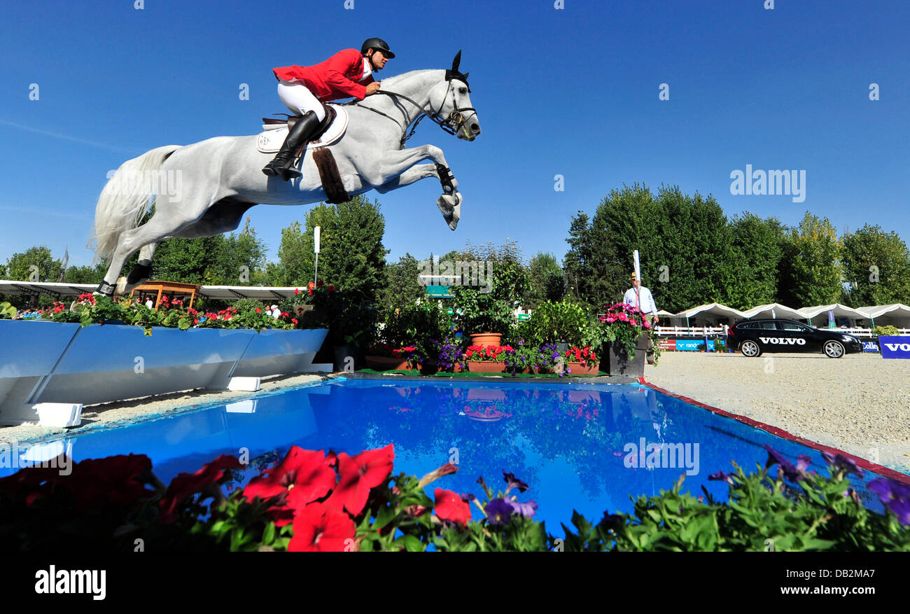 German show jumper Marco Kutscher jumps a water obstacle on his horse Cornet Obolensky at the European Show Jumping Stock Photo