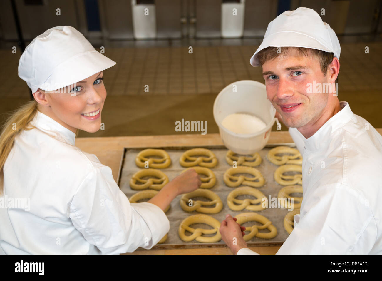 Two bakers in bakery or bakehouse baking pretzels - Stock Image