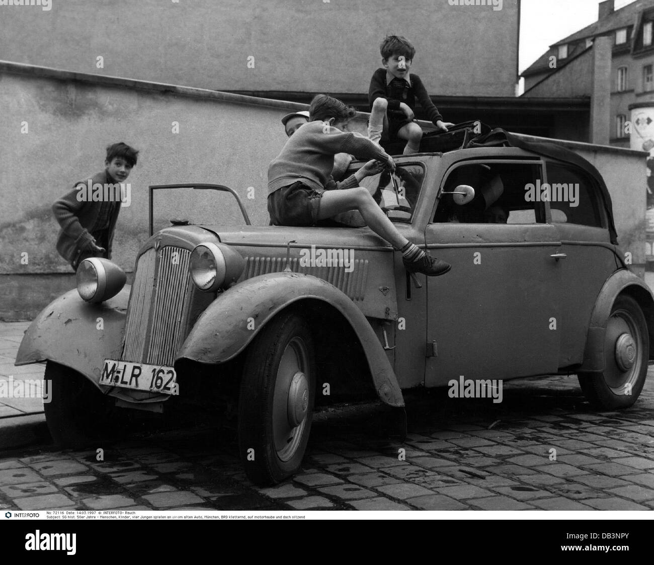 people, children, boys playing on an old car, Munich, Germany ...