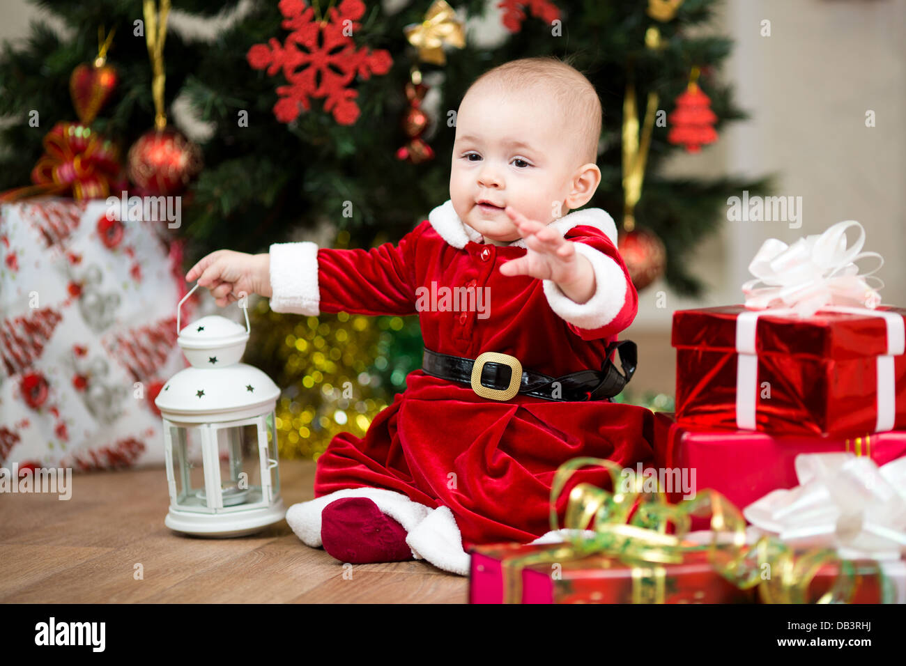 baby girl dressed as Santa Claus in front of Christmas tree with ...