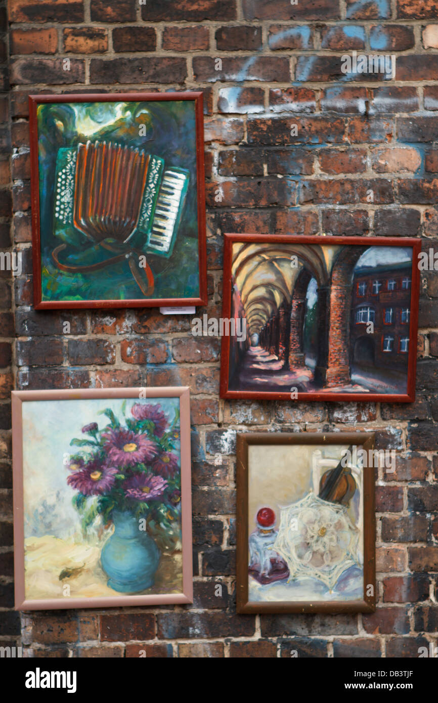 Naive paintings hanging on brick wall. Nikiszowiec, district of Katowice, Poland. - Stock Image