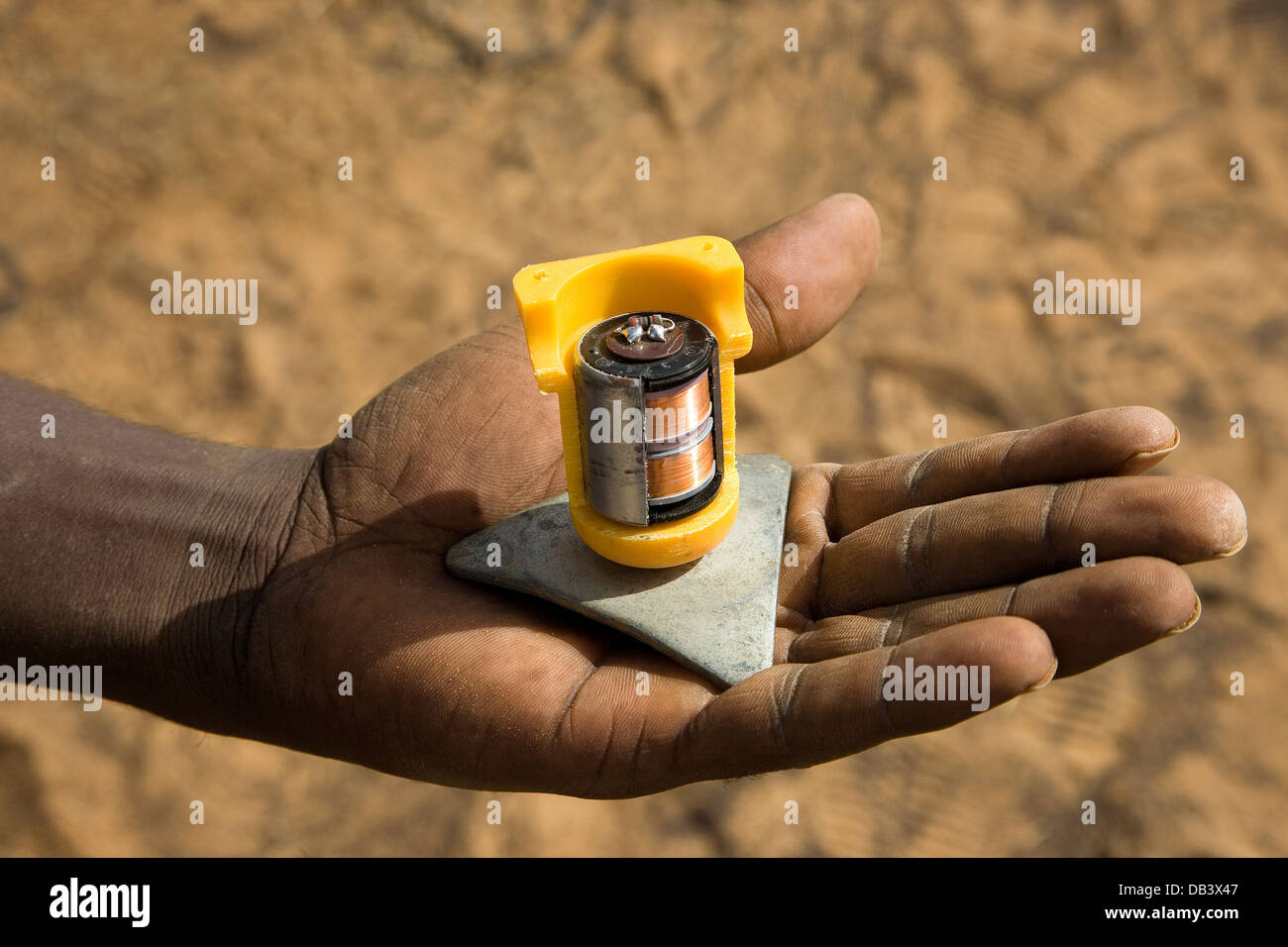 Cutaway of seismic geophone on the hand of Malian crewman to show detail and tripod base, Mali, West Africa - Stock Image