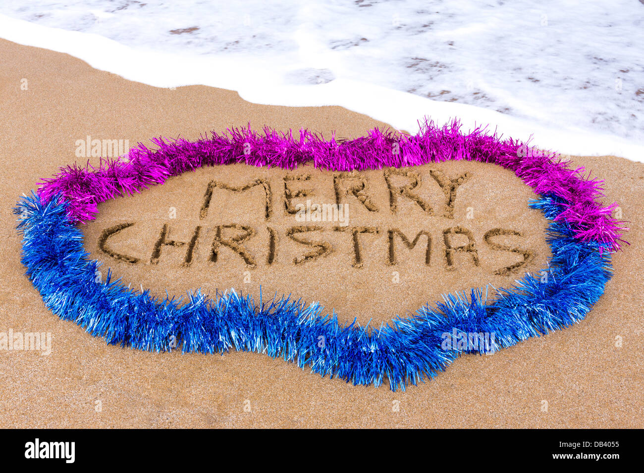 Merry Christmas written in sand with tinsel and sea in background - Stock Image