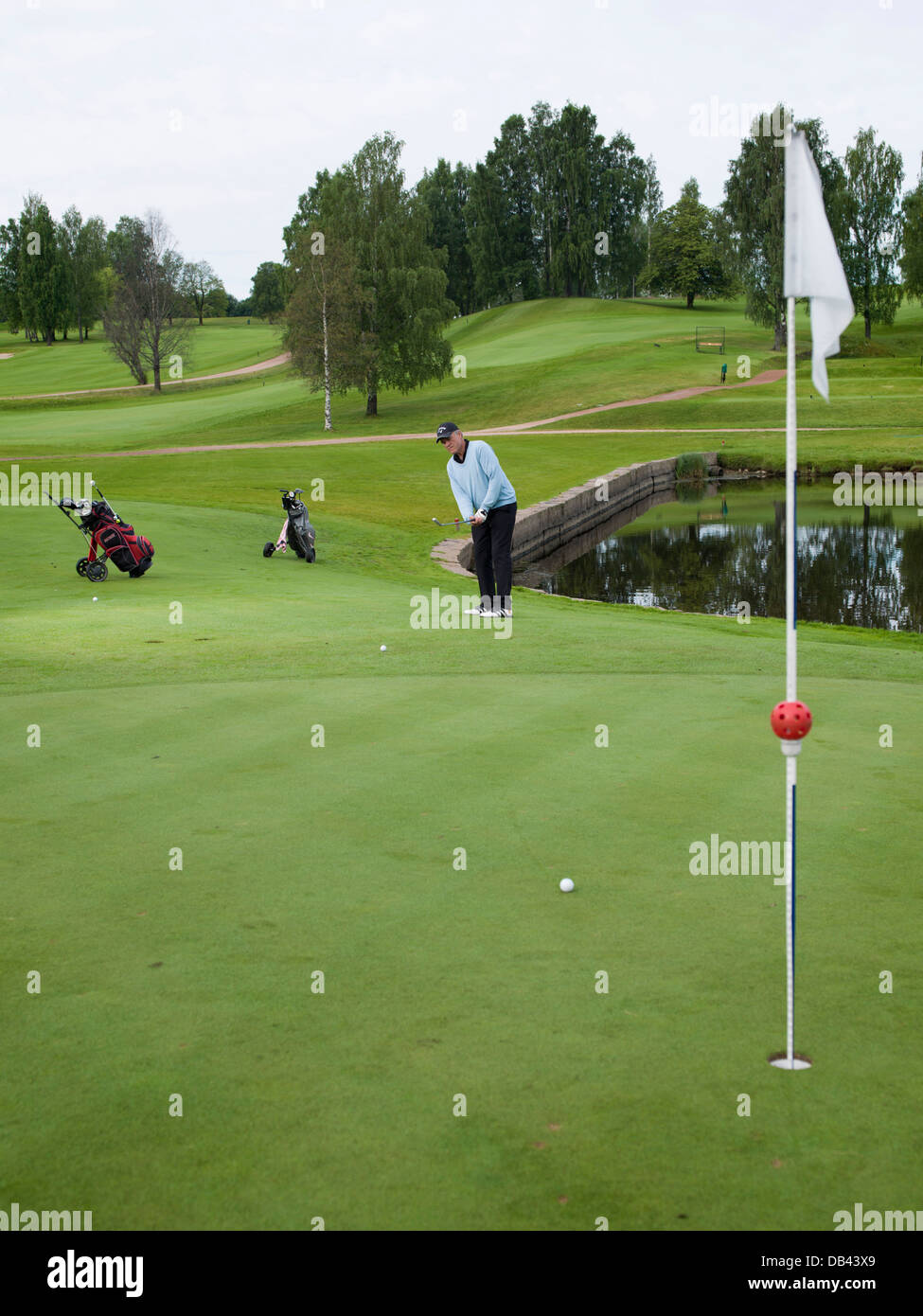 Senior citizen playing golf, dressed in black and blue, on the fairway - Stock Image