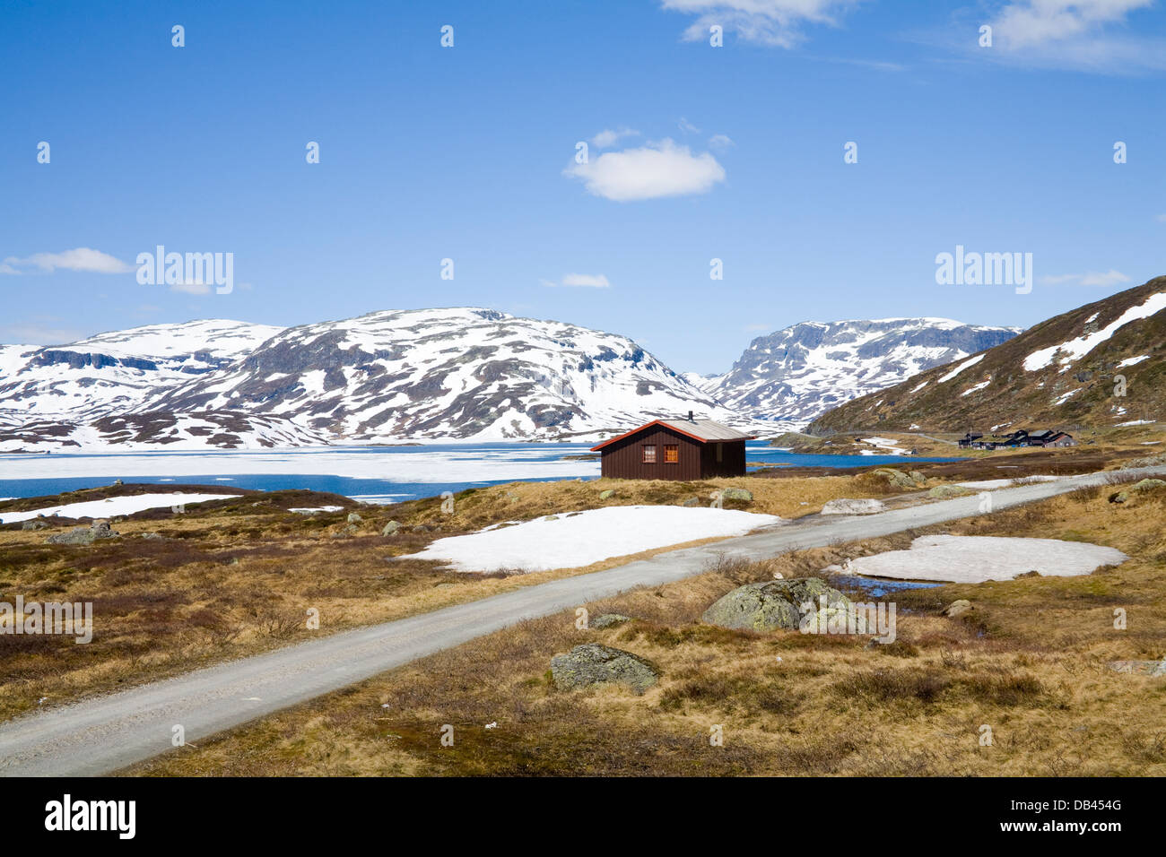 Telemark Norway Europe Refuge hut and holiday homes in wild moorland with lakes still frozen and snow covered mountains - Stock Image