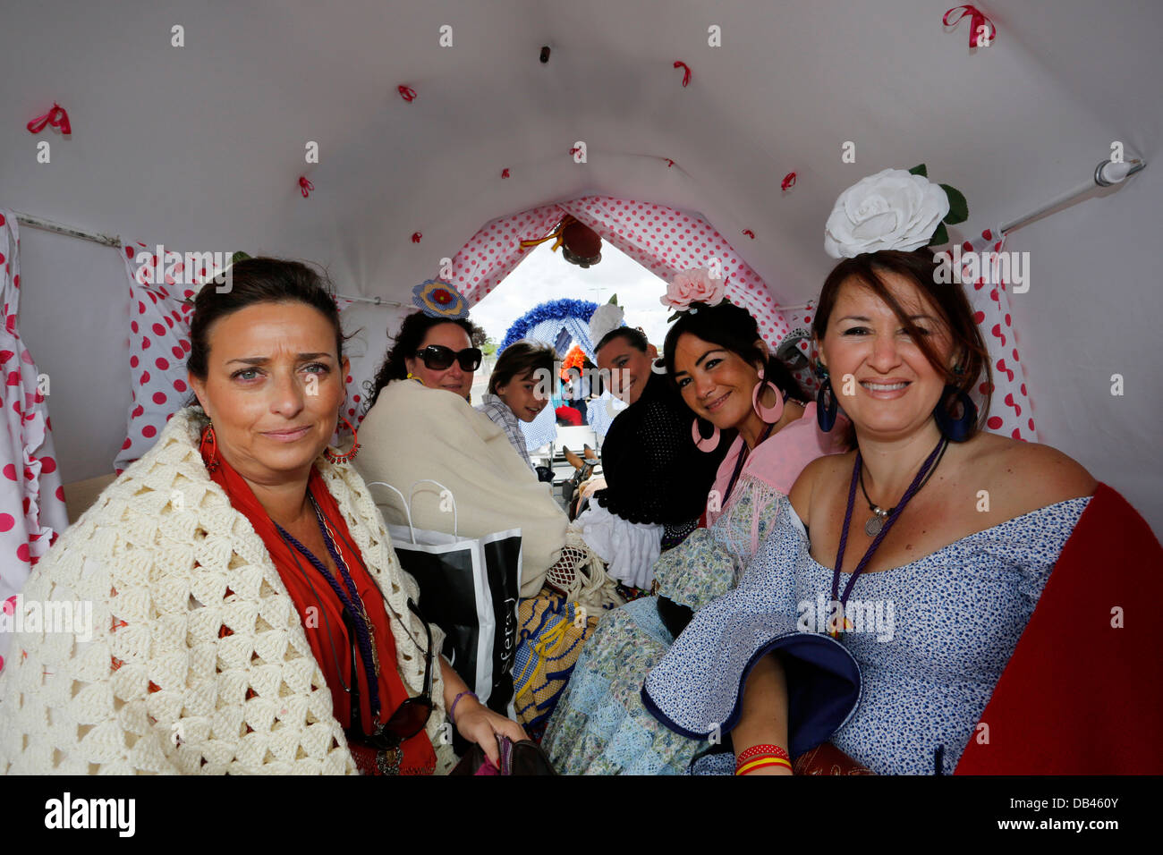 Women wearing Spanish Flamenco dresses in gypsy horse-drawn carriages on the pilgrimage route to El Rocio in Spain - Stock Image