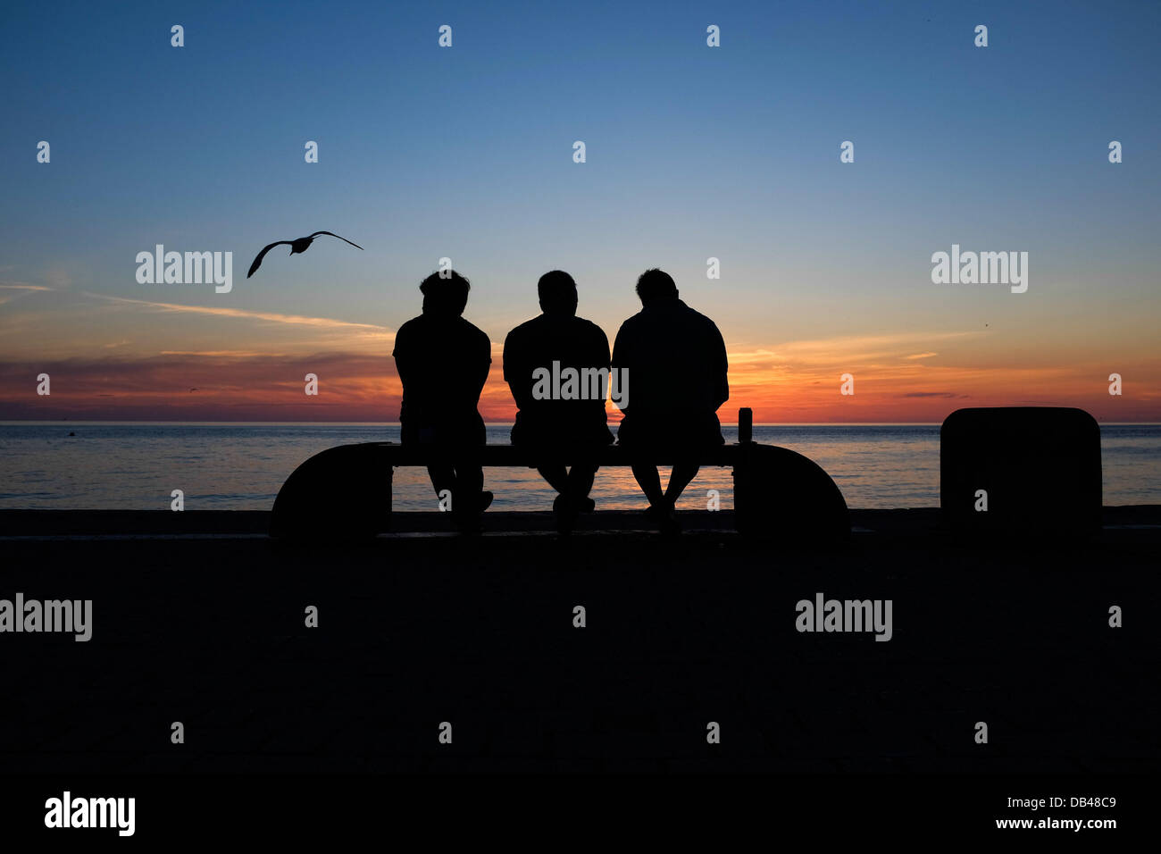 Aberystwyth, UK. 23rd July, 2013. Three men in silhouette sitting on a bench watching the sunset at Aberystwyth Stock Photo