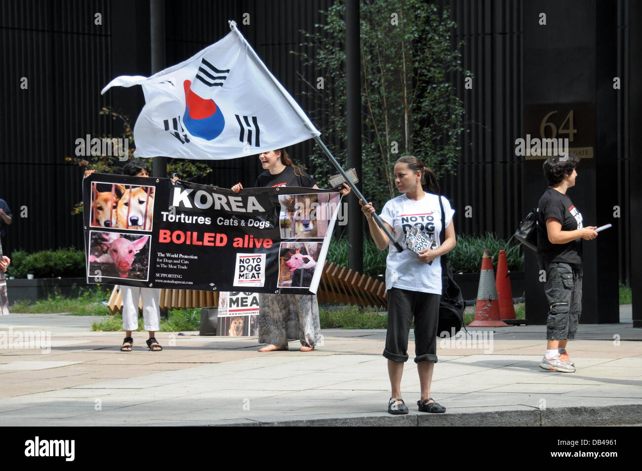 Actives waving a Korean flag protest against South Korean of the fifteen thousand dogs will be brutally killed every - Stock Image