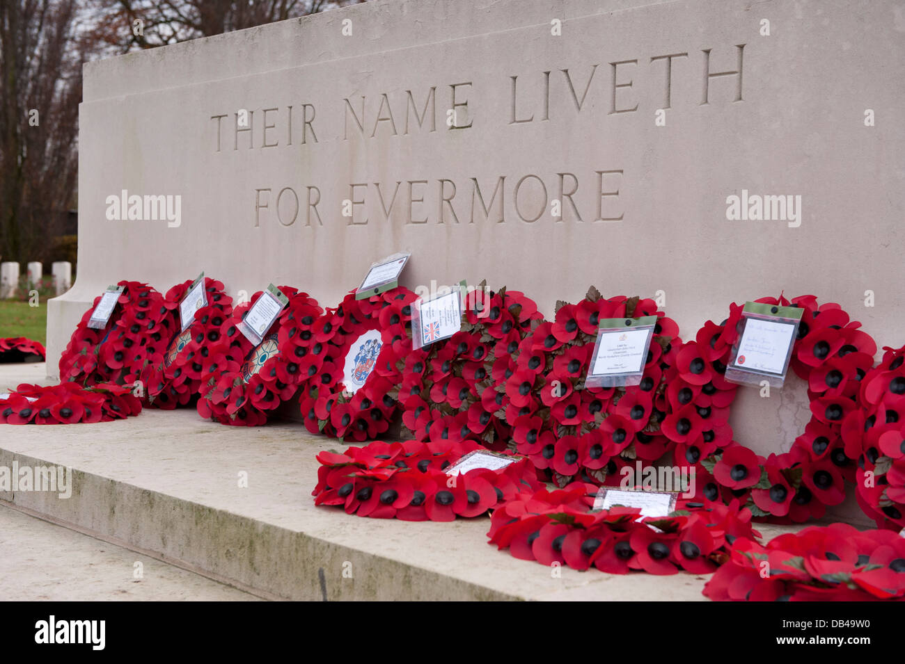 Circular red poppy wreaths on Stone of Remembrance after ceremony & inscription close-up - Stonefall Cemetery, - Stock Image