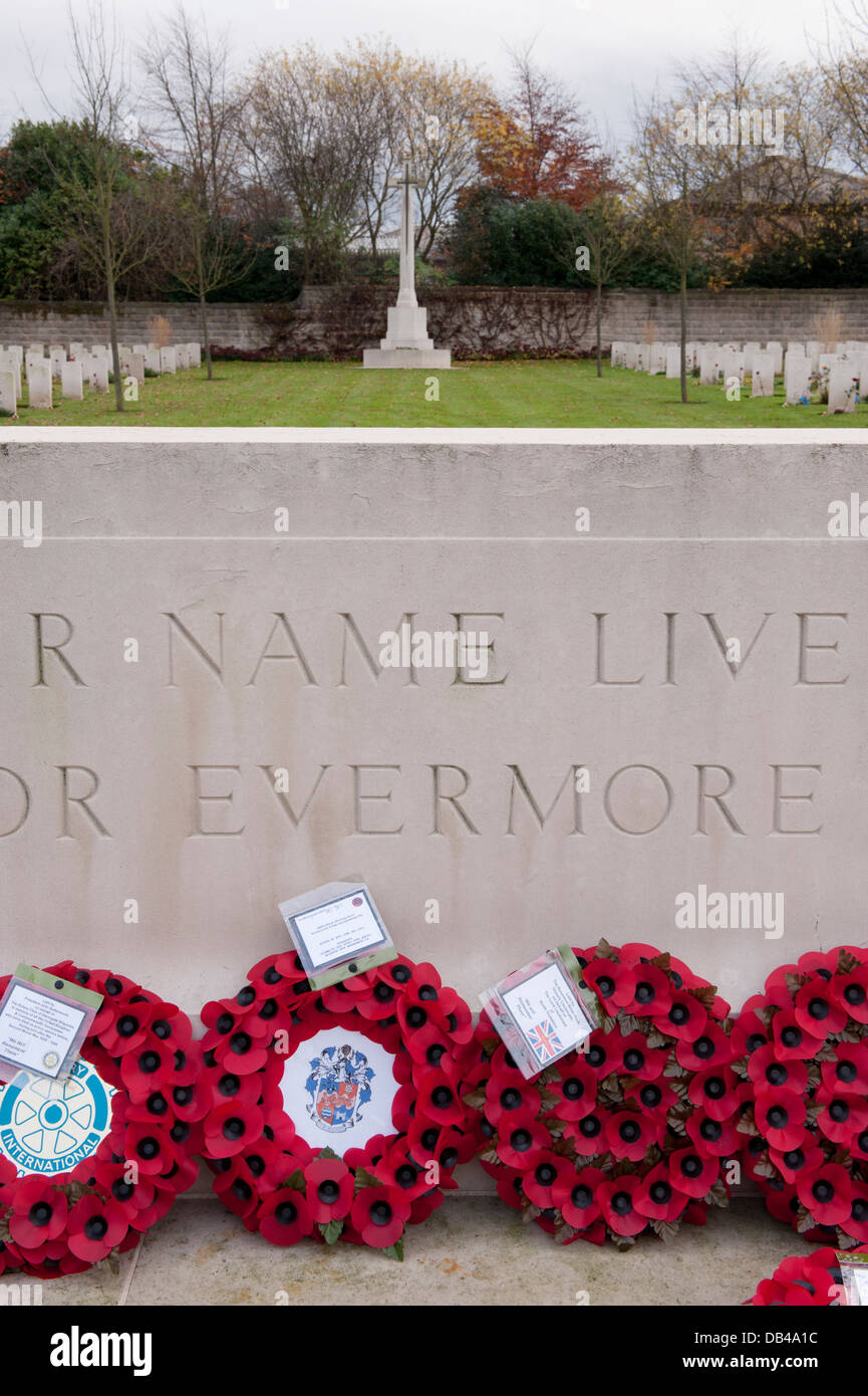 Cross, war graves & circular red poppy wreaths on Stone of Remembrance after ceremony - Stonefall Cemetery, Harrogate, Stock Photo