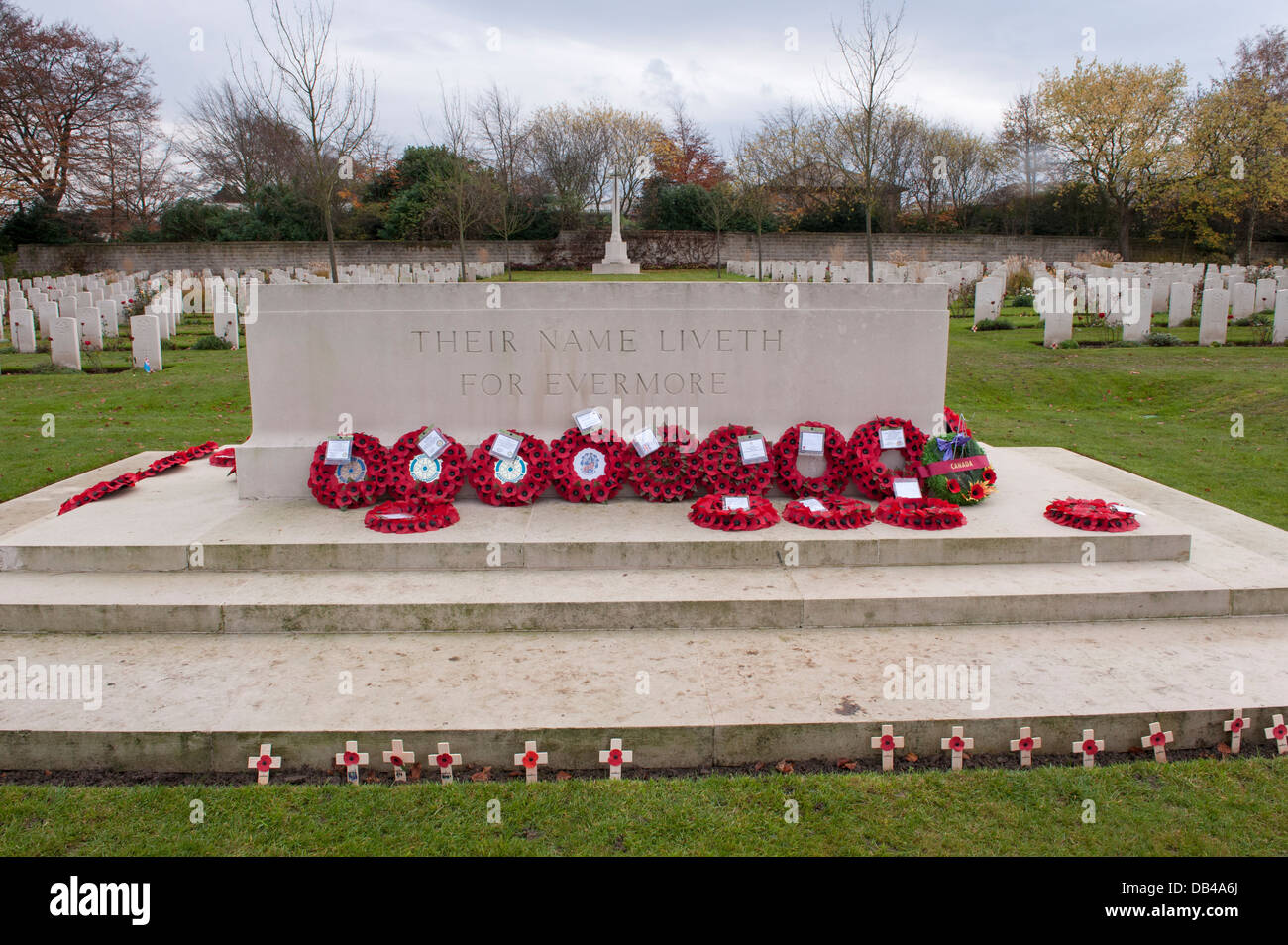 Rows of war graves & circular red poppy wreaths on Stone of Remembrance after ceremony - Stonefall Cemetery, Harrogate, Stock Photo