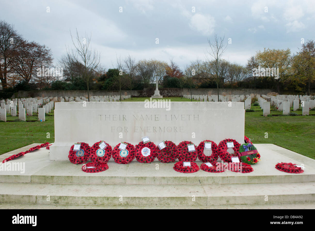Rows of war graves & red poppy wreaths laid on Stone of Rememberance after ceremony - Stonefall Cemetery, Harrogate, Stock Photo