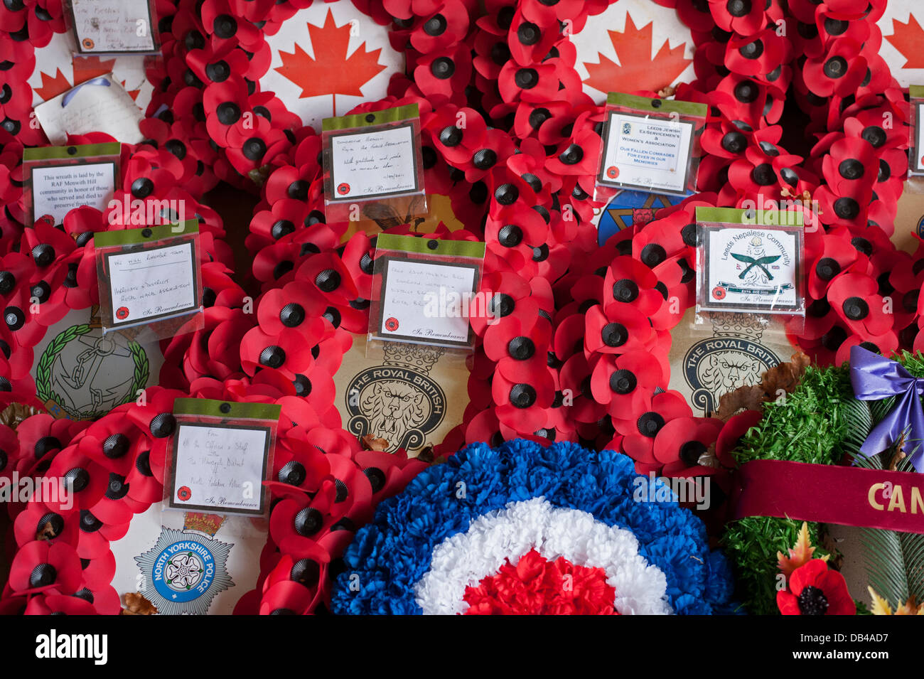 Close-up of poppy wreaths laid on memorial on Remembrance Day to commemorate war dead - Stonefall Cemetery, Harrogate, - Stock Image