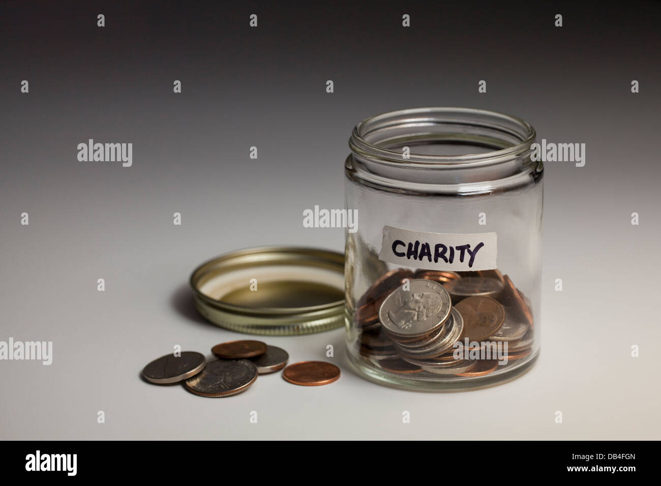Glass jar of coins saved for charity - USA - Stock Image