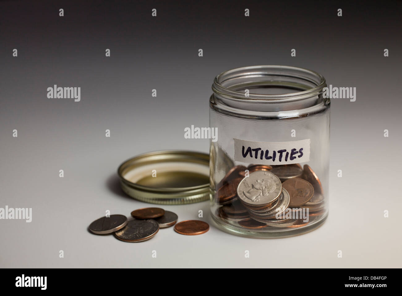 Coins in glass jar saved for utilities expenses - USA - Stock Image