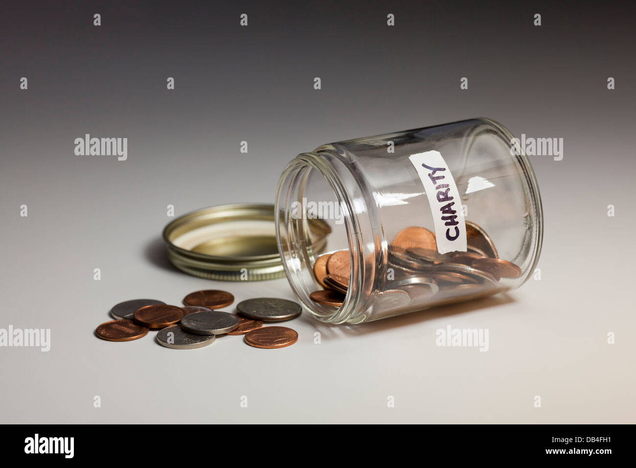 Spilled glass jar of coins saved for charity - USA - Stock Image